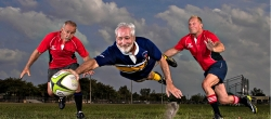 "Gary stretches for the goal line while supported by Rugby pals Mike ""Littleman"" Resta (left) and Harold Hickey (right)"