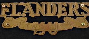 The Flanders 20 is a rather large badge from the grille of cars produced in Detroit in the early days of the American motorcar, and the 20 is presented in both numerals and is spelled out across a banner beneath the company name.