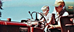 Warren Bogle gets a lesson in tractor driving from his father